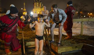 Russian Emergency Situations employees help a boy to bath in the icy water on Epiphany at the Church of the Holy Trinity in Ostankino near TV Tower in Moscow, Russia, Friday, Jan. 18, 2019. Across Russia, the devout and the daring are observing the Orthodox Christian feast day of Epiphany by immersing themselves in frigid water through holes cut through the ice of lakes and rivers. Epiphany celebrates the revelation of Jesus Christ as the incarnation of God through his baptism in the River Jordan. (AP Photo/Alexander Zemlianichenko)