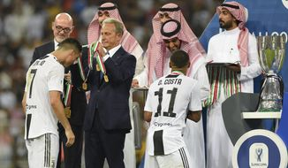 Juventus' Cristiano Ronaldo, left, and Juventus' Douglas Costa receive the winner medals end of the Italian Super Cup final soccer match between AC Milan and Juventus at King Abdullah stadium in Jiddah, Saudi Arabia, Wednesday, Jan. 16, 2019. (AP Photo)