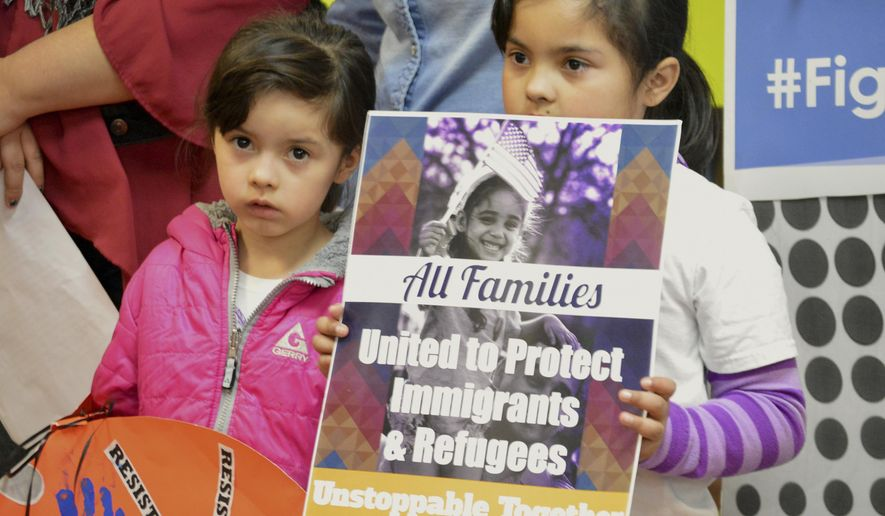 FILE - In this Jan. 25, 2017 file photo, Jocelynn Lujan, left, and her sister, Jennifer, attend a news conference in Albuquerque, N.M., where activists denounced President Donald Trump's executive actions on immigration. Identical Democratic proposals in the New Mexico House and Senate would prevent state agencies from cooperating with federal immigration authorities and limit the authority of sheriffs and jails to hold federal immigrant detainees. (AP Photo/Russell Contreras, File)