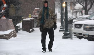 A man walks downtown during a snow storm in Sioux Falls, S.D., Friday, Jan. 18, 2019. A strong winter storm system is forecast to sweep across the Midwest into New England, bringing double-digit snow accumulations and high winds.(Loren Townsley/The Argus Leader via AP)