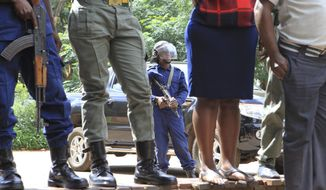 Armed riot police secure the area as pastor and activist Evan Mawarire, arrives at the magistrates courts in Harare, Zimbabwe, Friday, Jan. 18, 2019.   Zimbabwe Lawyers for Human Rights have said in a statement that Mawarire who is among the more than 600 people arrested this week has been charged with subverting a constitutional government amid a crackdown on protests against a dramatic fuel price increase.(AP Photo/Tsvangirayi Mukwazhi)