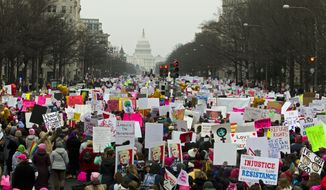 Demonstrators march on Pennsylvania Av. during the Women's March in Washington on Saturday, Jan. 19, 2019.  Organizers had originally planned to gather Saturday on the National Mall, but with the forecast calling for snow and freezing rain Saturday and the National Park Service no longer plowing the snow, the march's location and route was altered this week to start at Freedom Plaza and march down Pennsylvania Avenue past the Trump International Hotel.  (AP Photo/Jose Luis Magana)