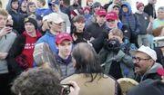 """In this Friday, Jan. 18, 2019, image made from video provided by the Survival Media Agency, a teenager wearing a """"Make America Great Again"""" hat, center left, stands in front of an elderly Native American singing and playing a drum in Washington. The Roman Catholic Diocese of Covington in Kentucky is looking into this and other videos that show youths, possibly from the diocese's all-male Covington Catholic High School, mocking Native Americans at a rally in Washington. (Survival Media Agency via AP)"""
