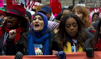 Co-presidents of the 2019 Women's March Linda Sarsour, center, and Tamika Mallory, right, march along with others demonstrators on Pennsylvania Av. during the Women's March in Washington on Saturday, Jan. 19, 2019.  The Women's March returned to Washington on Saturday and found itself coping with an ideological split and an abbreviated route due to the government shutdown. (AP Photo/Jose Luis Magana)