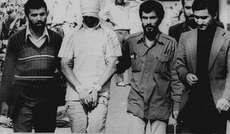 FILE - In this Nov. 9, 1979 file photograph, one of the hostages seized when Islamic radicals stormed the U.S. Embassy in Tehran, blindfolded and with his hands bound, is displayed to a crowd in Tehran, Iran. This climactic event and others in 1979, which dominated television sets and newspaper front pages 40 years ago, helped shape the modern Middle East. (AP Photo, File)