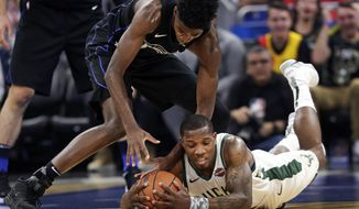 Orlando Magic's Jonathan Isaac, left, and Milwaukee Bucks' Eric Bledsoe go after a loose ball during the first half of an NBA basketball game, Saturday, Jan. 19, 2019, in Orlando, Fla. (AP Photo/John Raoux)