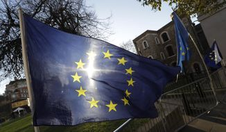 The sun shines through a European Union flag tied onto a railing near parliament in London, Thursday, Jan. 17, 2019. British Prime Minister Theresa May is reaching out to opposition parties and other lawmakers Thursday in a battle to put Brexit back on track after surviving a no-confidence vote. (AP Photo/Kirsty Wigglesworth)