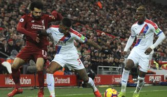 Liverpool's Mohamed Salah, left, and Crystal Palace's Patrick van Aanholt challenge for the ball during the English Premier League soccer match between Liverpool and Crystal Palace at Anfield in Liverpool, England, Saturday, Jan. 19, 2019. (AP Photo/Rui Vieira)