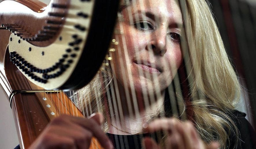 In this Jan. 11, 2019 photo, harpist Lauren Meier plays her Venus traditional harp at her home in Grand Island, Neb. Meier and her husband moved to Grand Island last June. (Barrett Stinson/The Independent via AP)