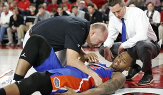 Florida forward Keith Stone (25) is checked on by a trainer and Florida coach Mike White after going down with a leg injury during an NCAA college basketball game against Georgia in Athens, Ga., on Saturday, Jan. 19, 2019.  (Joshua L. Jones/Athens Banner-Herald via AP)