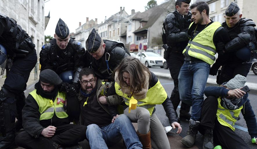 """Police remove yellow vest demonstrators staging a sit-down protest in Souillac, southern France, ahead of French President Emmanuel Macron' s visit, Friday, Jan. 18, 2019. Macron is meeting Friday with about 600 mayors and local officials in Souillac, a small town in southwestern France, as part of a national """"grand debate"""".(AP Photo/Fred Scheiber)"""