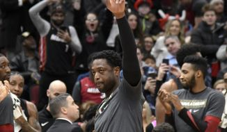 Miami Heat guard Dwyane Wade (3) gestures to the crowd after being honored during the first half of an NBA basketball game against the Chicago Bulls, Saturday, Jan. 19, 2019, in Chicago. (AP Photo/David Banks)