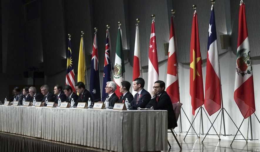 Toshimitsu Motegi, Japan's minister of economy, trade, and industry, sits with other ministers and delegates of a Pacific Rim trade bloc, attend a joint press conference after a session of the Comprehensive and Progressive Trans-Pacific Partnership (CPTPP) in Tokyo Saturday, Jan. 19, 2019. Trade ministers of a Pacific Rim trade bloc are meeting in Tokyo, gearing up to roll out and expand the market-opening initiative. (AP Photo/Eugene Hoshiko)