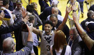 West Virginia guard James Bolden (3) celebrates at the conclusion of an NCAA college basketball game against Kansas Saturday, Jan. 19, 2019, in Morgantown, W.Va. West Virginia defeated Kansas 65-64. (AP Photo/Raymond Thompson)