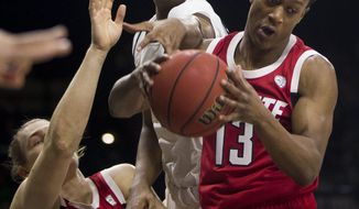 North Carolina State's C.J. Bryce (13) grabs a rebound over teammate Wyatt Walker (33) and Notre Dame's D.J. Harvey during the first half of an NCAA college basketball game Saturday, Jan. 19, 2019, in South Bend, Ind. (AP Photo/Robert Franklin)