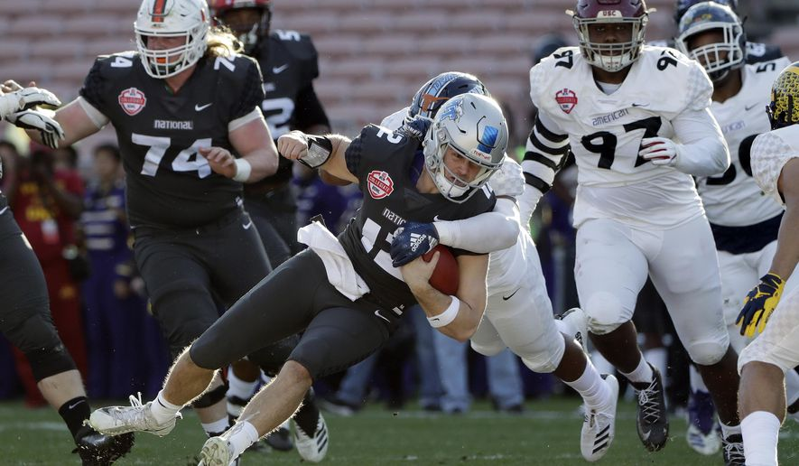 National Team quarterback Brent Stockstill, center, is tackled as he carries against the American Team during the first half of the NFLPA Collegiate Bowl football game Saturday, Jan. 19, 2019, in Pasadena, Calif. (AP Photo/Marcio Jose Sanchez)