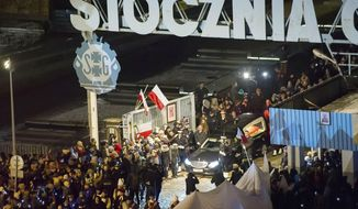 A black hearse with the coffin of the slain mayor of the city of Gdansk Pawel Adamowicz, followed by a procession of residents, is being brought to St. Mary's Basilica for Saturday's burial, in Gdansk, Poland, on Friday, Jan. 18, 2019. Church bells tolled as tens of thousands in Poland's northern city of Gdansk walked in a procession Friday bringing the coffin of the city's slain mayor to a basilica on the eve of his burial. (AP Photo/Wojciech Strozyk)