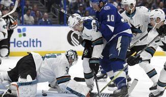 San Jose Sharks goaltender Martin Jones (31) looks to cover as center Logan Couture (39) and Tampa Bay Lightning center J.T. Miller (10) fight for the puck during the second period of an NHL hockey game Saturday, Jan. 19, 2019, in Tampa, Fla. (AP Photo/Jason Behnken)