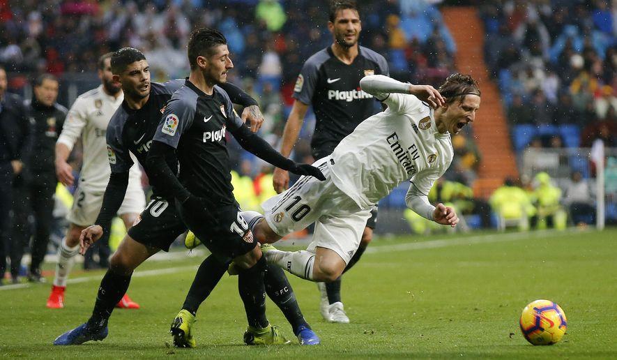 Real Madrid's Luka Modric, right, is tackled by Sevilla's Sergio Escudero during La Liga soccer match between Real Madrid and Sevilla at the Bernabeu stadium in Madrid, Spain, Saturday, Jan. 19, 2019. (AP Photo/Andrea Comas)