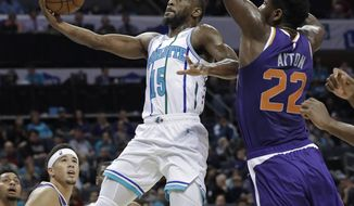 Charlotte Hornets' Kemba Walker (15) drives past Phoenix Suns' Deandre Ayton (22) during the first half of an NBA basketball game in Charlotte, N.C., Saturday, Jan. 19, 2019. (AP Photo/Chuck Burton)
