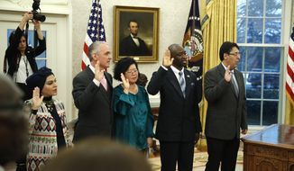 The five people being naturalized as American citizen, take the oath of allegiance in the Oval Office of the White House, in Washington, Saturday, Jan. 19, 2019. (AP Photo/Alex Brandon)