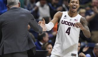 Connecticut's Jalen Adams (4) celebrates with head coach Dan Hurley during the second half of an NCAA college basketball game against Tulane, Saturday, Jan. 19, 2019, in Storrs, Conn. (AP Photo/Jessica Hill) ** FILE **