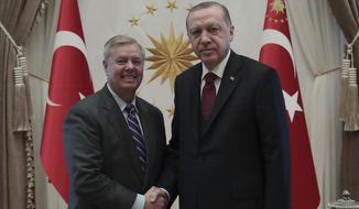 Turkey's President Recep Tayyip Erdogan, right, and U.S. Republican Senator Lindsey Graham shake hands before a meeting in Ankara, Turkey, Friday, Jan. 18, 2019. Erdogan and Graham has discussed the situation in Syria as the United States prepares to withdraw troops.(Presidential Press Service via AP, Pool)