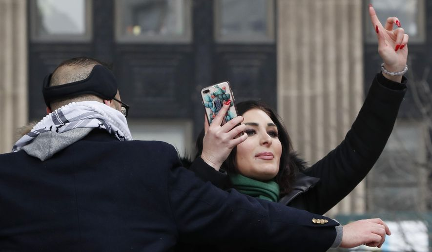 Political activist Laura Loomer, right, films herself on her smartphone as she is escorted off the stage after interrupting Women's March NYC director Agunda Okeyo at a rally in Lower Manhattan, Saturday, Jan. 19, 2019, in New York. (AP Photo/Kathy Willens)