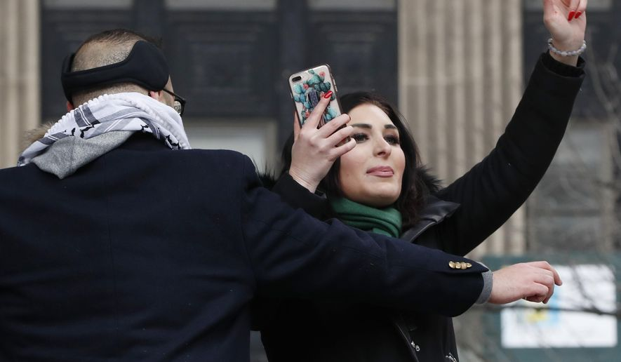 Political activist Laura Loomer, right, films herself on her smartphone as she is escorted off the stage after interrupting Women's March NYC director Agunda Okeyo at a rally in Lower Manhattan, Saturday, Jan. 19, 2019, in New York. (AP Photo/Kathy Willens) **FILE**