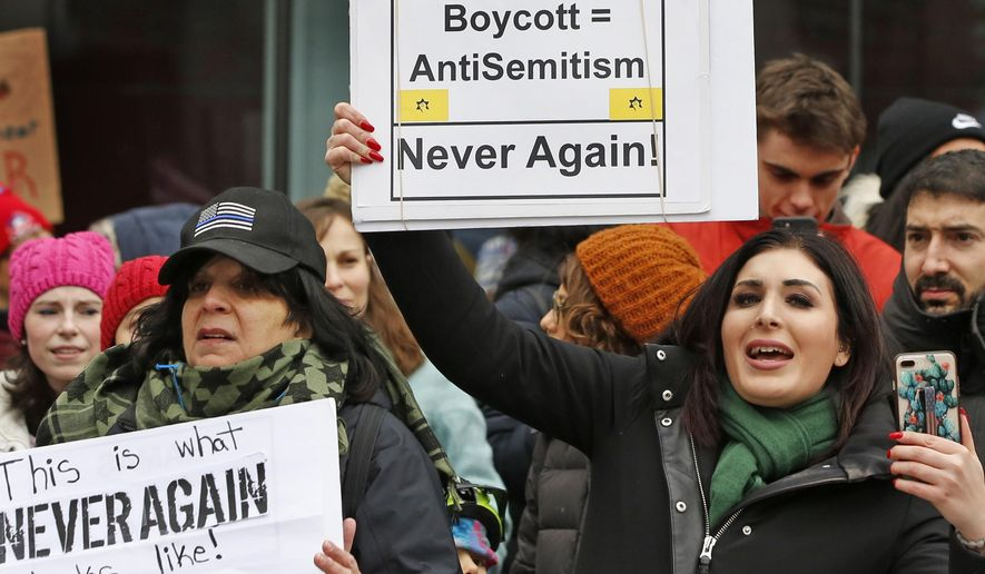 Political activist Laura Loomer, right, holds a sign across the street from a rally organized by Women's March NYC after she barged onto the stage interrupting Women's March NYC director Agunda Okeyo who was speaking during a rally in Lower Manhattan, Saturday, Jan. 19, 2019, in New York. Loomer was escorted off the stage after the incident. (AP Photo/Kathy Willens)