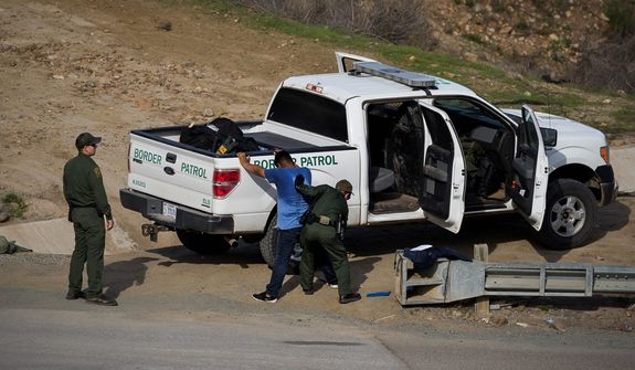 A Honduran asylum seeker was stopped by U.S. Border Patrol agents after he crossed from Tijuana, Mexico, to San Diego. Many Central American migrants have become discouraged by the long wait to apply for asylum through official ports of entry. (Associated Press/File)
