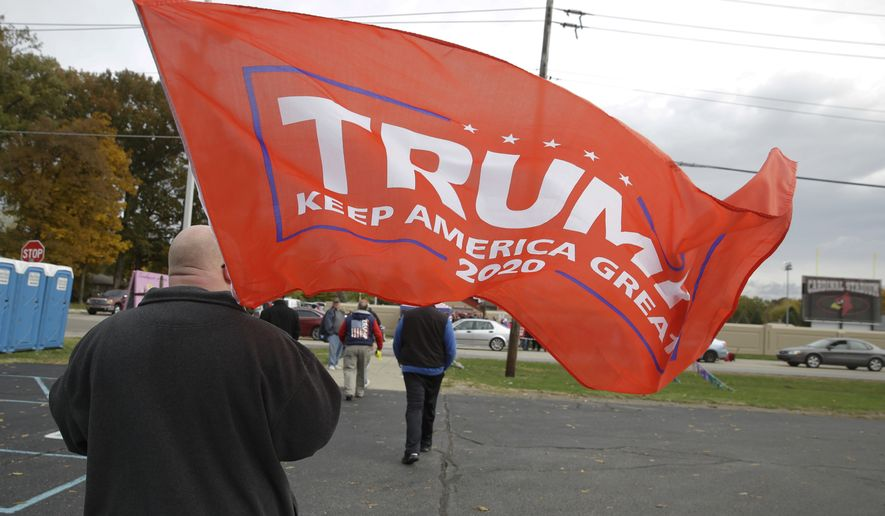 A Trump supports carries a flag as he makes his way to a campaign rally featuring President Donald Trump in Indianapolis, Friday, Nov. 2, 2018. (AP Photo/Michael Conroy)