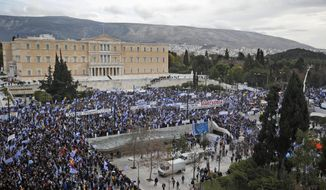 Protestors wave Greek flags outside parliament in Athens, Sunday, Jan. 20, 2019. Greece's Parliament is to vote this coming week on whether to ratify the agreement that will rename its northern neighbor North Macedonia. Macedonia has already ratified the deal, which, polls show, is opposed by a majority of Greeks. (AP Photo/Thanassis Stavrakis)