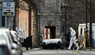 "Forensic investigators at the scene of a car bomb blast on Bishop Street in Londonderry, Northern Ireland, Sunday, Jan. 20, 2019. Northern Ireland police and politicians have condemned a ""reckless"" car bombing outside a courthouse in the city of Londonderry. The device was placed inside a hijacked delivery vehicle and exploded Saturday night as police, who had received a warning, were evacuating the area. There were no reports of injuries. (Niall Carson/PA via AP)"