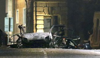 This photo taken on Saturday, Jan. 19, 2019 shows the scene of a suspected car bomb on Bishop Street in Londonderry, Northern Ireland. Northern Ireland politicians are condemning a car bombing outside a courthouse in the city of Londonderry. The device exploded Saturday night as police, who had received a warning, were evacuating the area. The Police Service of Northern Ireland posted a photograph of a vehicle in flames and urged the public to stay away. (Steven McAuley/PA via AP)
