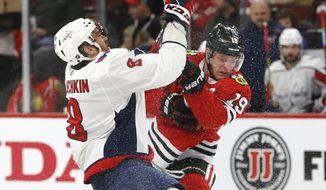 Left Washington Capitals left wing Alex Ovechkin (8) and Chicago Blackhawks center Jonathan Toews (19) battle for the puck during the first period of an NHL hockey game Sunday, Jan. 20, 2019, in Chicago. (AP Photo Nuccio DiNuzzo)