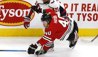 Chicago Blackhawks right wing John Hayden (40) tries to get to a puck ahead of Washington Capitals right wing Devante Smith-Pelly (25) during the third period of an NHL hockey game Sunday, Jan. 20, 2019, in Chicago. (AP Photo Nuccio DiNuzzo)