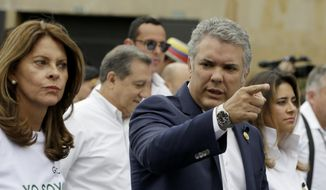 Colombia's President Ivan Duque and Vice President Marta Lucia Ramirez, left, take part in a march to repudiate terrorism in Bogota, Colombia, Sunday, Jan. 20, 2019. A car bombing at a Bogota police academy that authorities have attributed to rebels of the National Liberation Army killed 21 people and left dozens more wounded on Jan. 17. (AP Photo/Fernando Vergara) ** FILE **