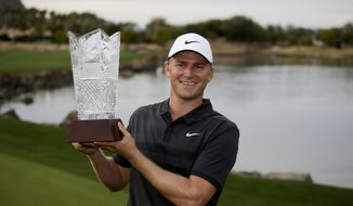 Adam Long holds the trophy on the 18th green after winning the Desert Classic golf tournament on the Stadium Course at PGA West on Sunday, Jan. 20, 2019, in La Quinta, Calif. (AP Photo/Chris Carlson)
