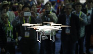 FILE - In this Jan. 7, 2016 file photo a drone hovers at the DJI booth during CES International in Las Vegas. The skies around Nevada's largest cities are about to see more drones, after federal agencies picked the state for testing remote-controlled aircraft in urban airspace. The Federal Aviation Administration and U.S. Department of Transportation announced Jan. 15, 2019, that the Nevada UAS Test Site Smart Silver State program will oversee testing in Reno and Henderson.(AP Photo/John Locher, File)