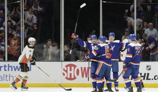 New York Islanders' Cal Clutterbuck, second from left, celebrates with teammates after scoring a goal as Anaheim Ducks' Cam Fowler (4) skates past during the first period of an NHL hockey game Sunday, Jan. 20, 2019, in Uniondale, N.Y. (AP Photo/Frank Franklin II)