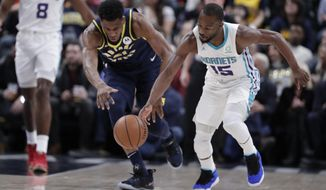 Charlotte Hornets guard Kemba Walker (15) steals the ball from Indiana Pacers forward Thaddeus Young (21) during the first half of an NBA basketball game in Indianapolis, Sunday, Jan. 20, 2019. (AP Photo/Michael Conroy)