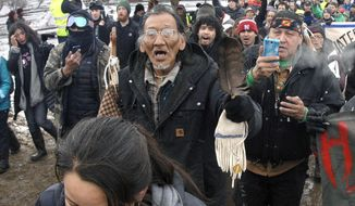 In this Feb. 22, 2017, file photo, a large crowd representing a majority of the remaining Dakota Access Pipeline protesters, including Nathan Phillips, center with glasses, march out of the Oceti Sakowin camp before the deadline set for evacuation of the camp near Cannon Ball, N.D. Phillips says he felt compelled to get between a group of black religious activists and largely white students with his ceremonial drum to defuse a potentially dangerous situation at a rally in Washington. (Mike McCleary/The Bismarck Tribune via AP, File)