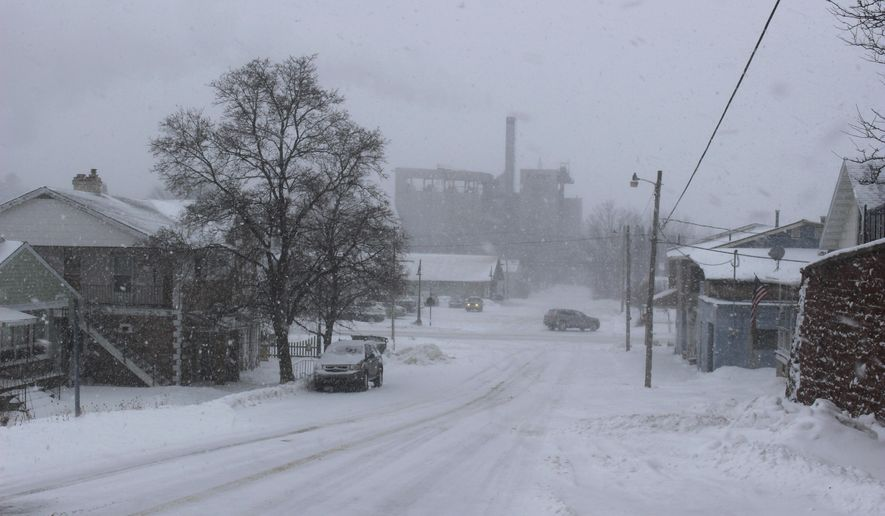 In this Jan. 9, 2019 photo, the L'Anse Warden Power Plant looms over the village of L'Anse, Mich., in the snow. Members of the community group Friends of the Land of Keweenaw (FOLK), are concerned that new fuel pellets could bring new toxicity to the air in L'Anse. (Joshua Vissers/The Mining Journal via AP)