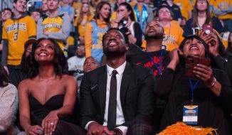 Miami Heat player and Marquette alumni Dwyane Wade, center, is honored with Dwyane Wade Day during half time as Marquette takes on Providence for an NCAA college basketball game Sunday, Jan. 20, 2019, in Milwaukee. (AP Photo/Darren Hauck)