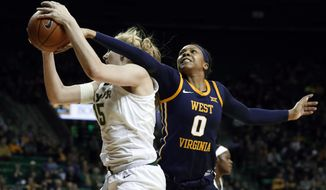 Baylor forward Lauren Cox (15) comes down with a defensive rebound in front of West Virginia forward Naomi Davenport (0) in the first half of an NCAA college basketball game, Sunday, Jan. 20, 2019, in Waco, Texas. (AP Photo/Tony Gutierrez)