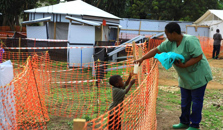 """A health worker feeds a boy suspected of having the Ebola virus at treatment center in Beni, Eastern Congo on Sept. 9, 2018. Responders are seeing """"sporadic"""" cases of Ebola in four cities. (ASSOCIATED PRESS)"""