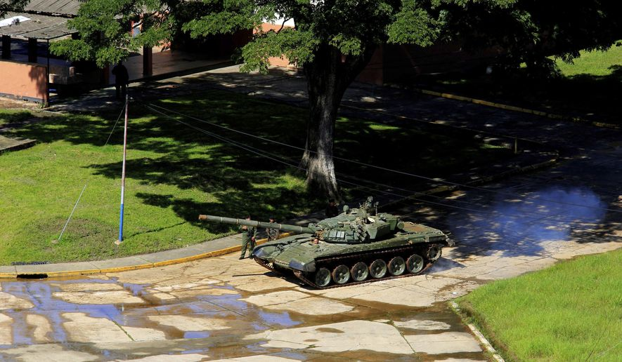 """A tank of Venezuelan Bolivarian National Army moves inside the Military base Paramacay in Valencia, Venezuela, Sunday, Aug. 6, 2017. Venezuelan ruling party chief Diosdado Cabello said the military squashed a """"terrorist"""" attack at the military base Sunday, shortly after a small group of men dressed in military fatigues released a video declaring themselves in rebellion.(AP Photo/Juan Carlos Hernandez)"""