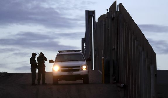 In this Wednesday, Nov. 21, 2018, file photo, United States Border Patrol agents stand by a vehicle near one of the border walls separating Tijuana, Mexico, and San Diego, in San Diego. (AP Photo/Gregory Bull, File)