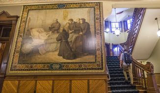 This Nov. 29, 2017, photo shows a mural of Christopher Columbus at Notre Dame in South Bend, Ind. The University of Notre Dame will cover murals in a campus building that depict Christopher Columbus in America, the school's president said, following criticism that the images depict Native Americans in stereotypical submissive poses before white European explorers. (Robert Franklin/South Bend Tribune via AP)